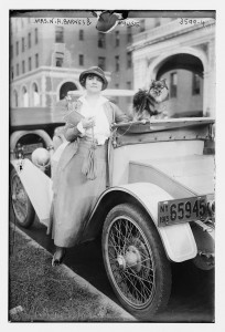Photo of woman and child standing by an antique car