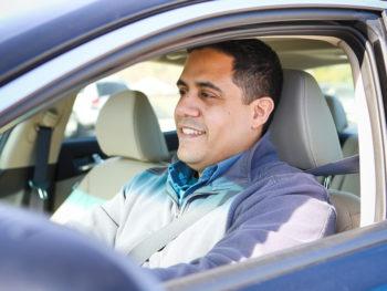 man smiling sitting in vehicle driver seat