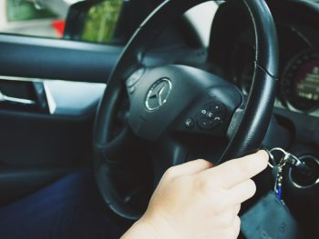 photo of hands holding a car steering wheel