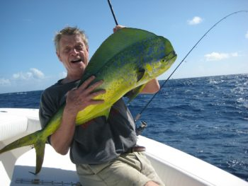 photo of a man holding a large fish on a boat