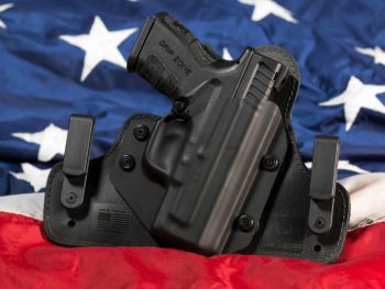 photo of gun in a holster in front of american flag