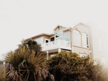 photo of a beach house on a hill covered in trees and sea oats